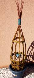 Oiseau émaillé bleu vert dans son tressage d'osier